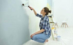 mujer al preparar una pared para aplicar una imprimación